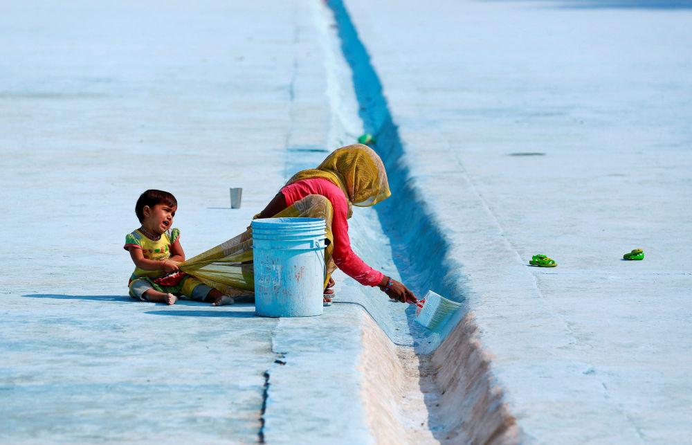 Dziecko przeszkadza pracującej matce w indyjskim Delhi