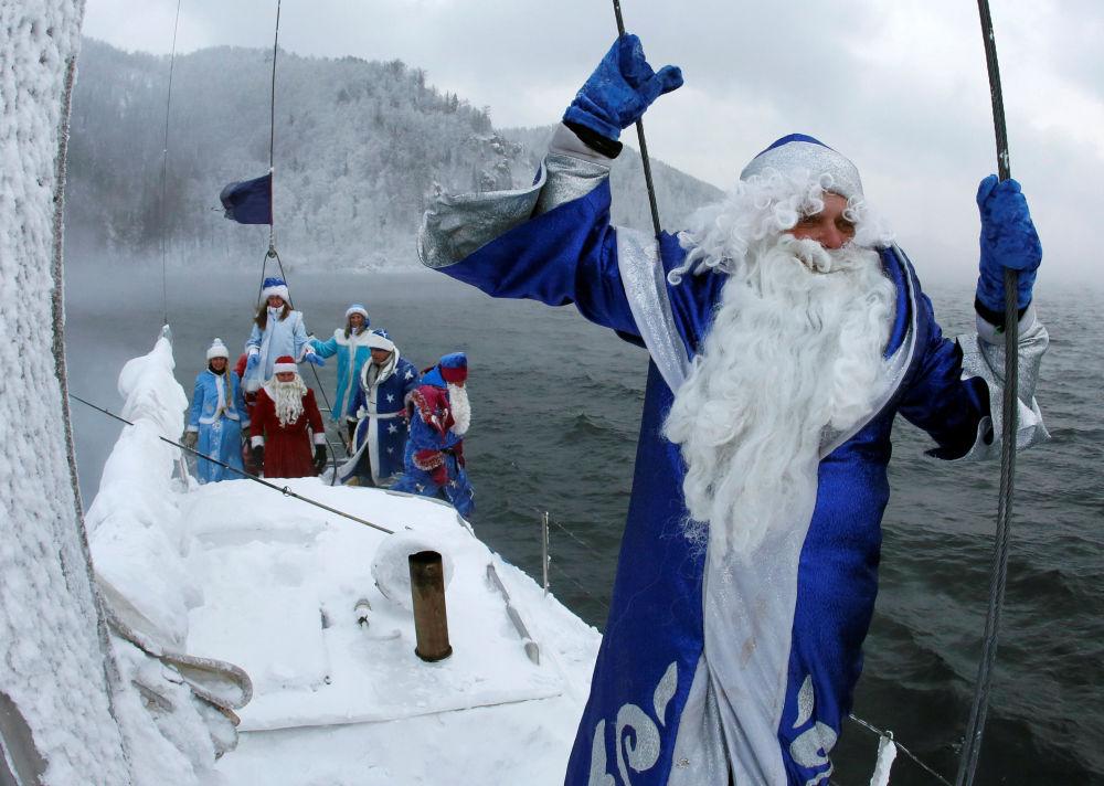 Członkowie klubu żeglarskiego Skipper przebrani za Świętego Mikołaja i Śnieżynkę płyną po rzece Jenisiej niedaleko Krasnojarska