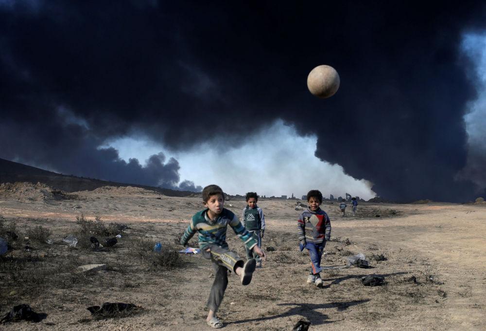 Chłopcy grający w piłkę nozną na południu od Mosulu na tle dymu od palącej się ropy