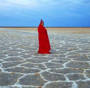 Kobieta na słonym jeziorze niedaleko pustyni Mesr w Iranie