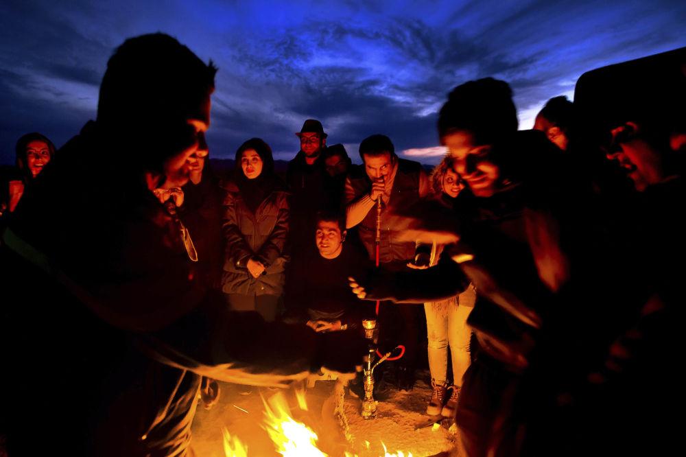 Turyści przy ognisku na irańskiej pustyni Mesr