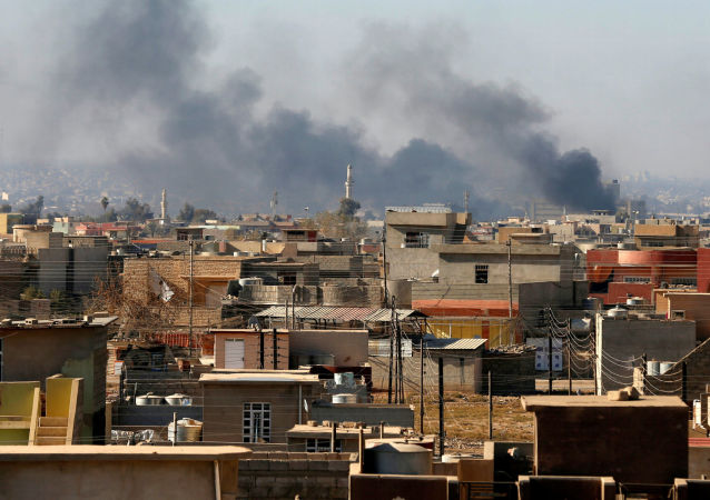 Dym nad domami w irackim Mosulu