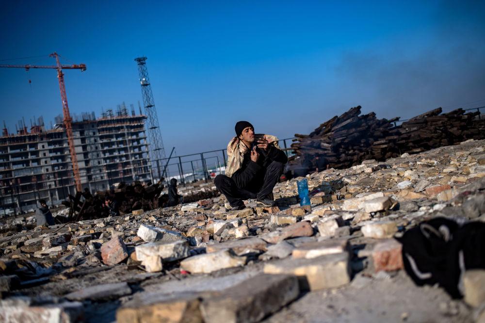 Uchodźca goli się przy tymczasowym schronieniu w opuszczonym magazynie w Belgradzie