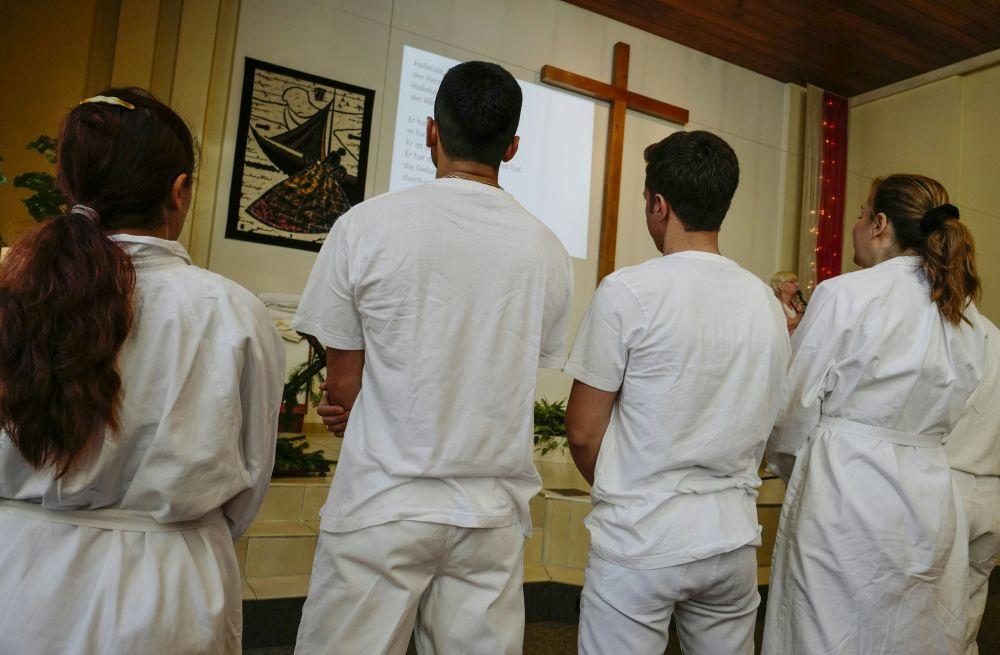 Obrzęd chrztu czterech uchodźców muzułmanów z Afganistanu i Iranu w kościele w Berlinie