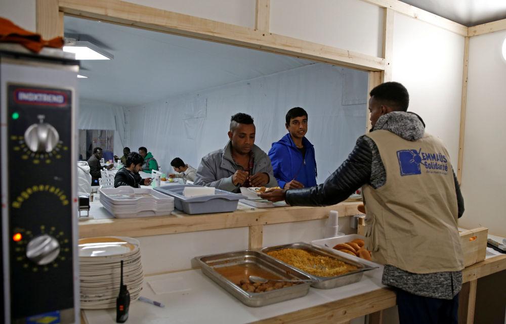 Wolontariusz rozdaje jedzenie w ośrodku dla uchodźców na północy Paryża