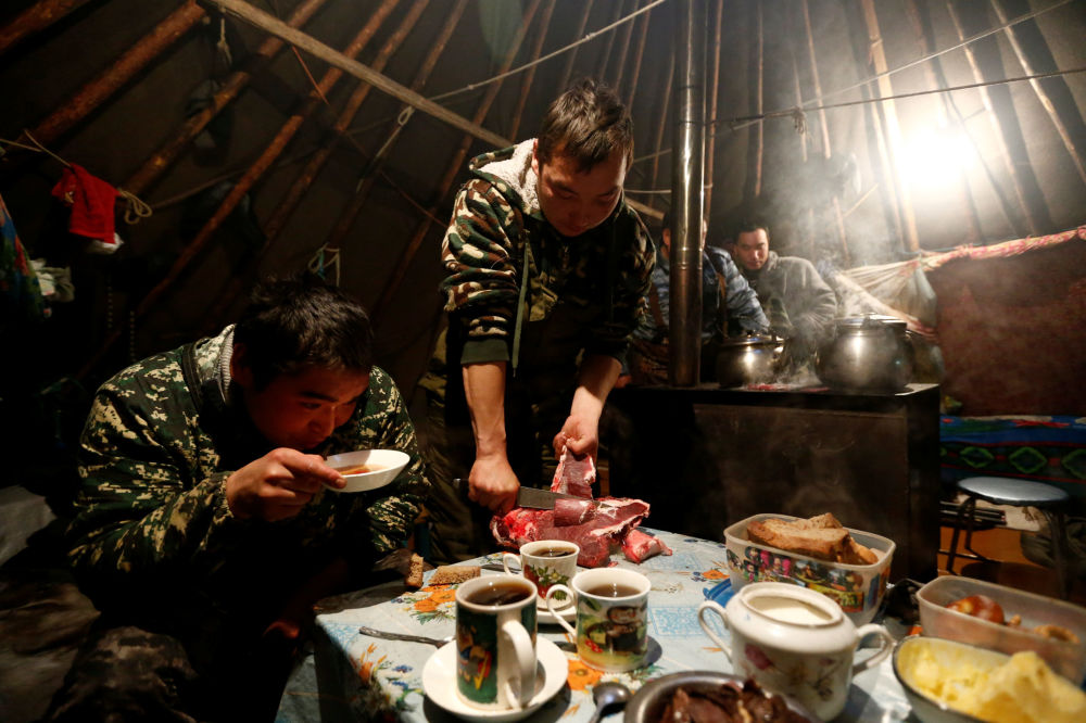 Hodowcy reniferów przy posiłku w czumie pośród tundry w Nienieckim Okręgu Autonomicznym