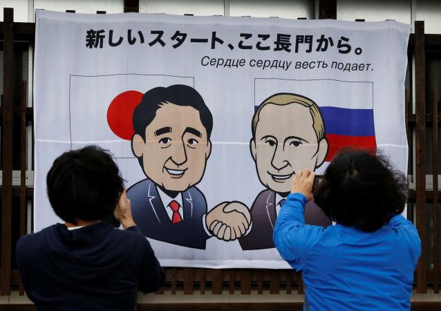 Ludzie fotografują plakat z podobizną prezydenta Rosji Władimira Putina i premiera Japonii Shinzo Abe w Nagato