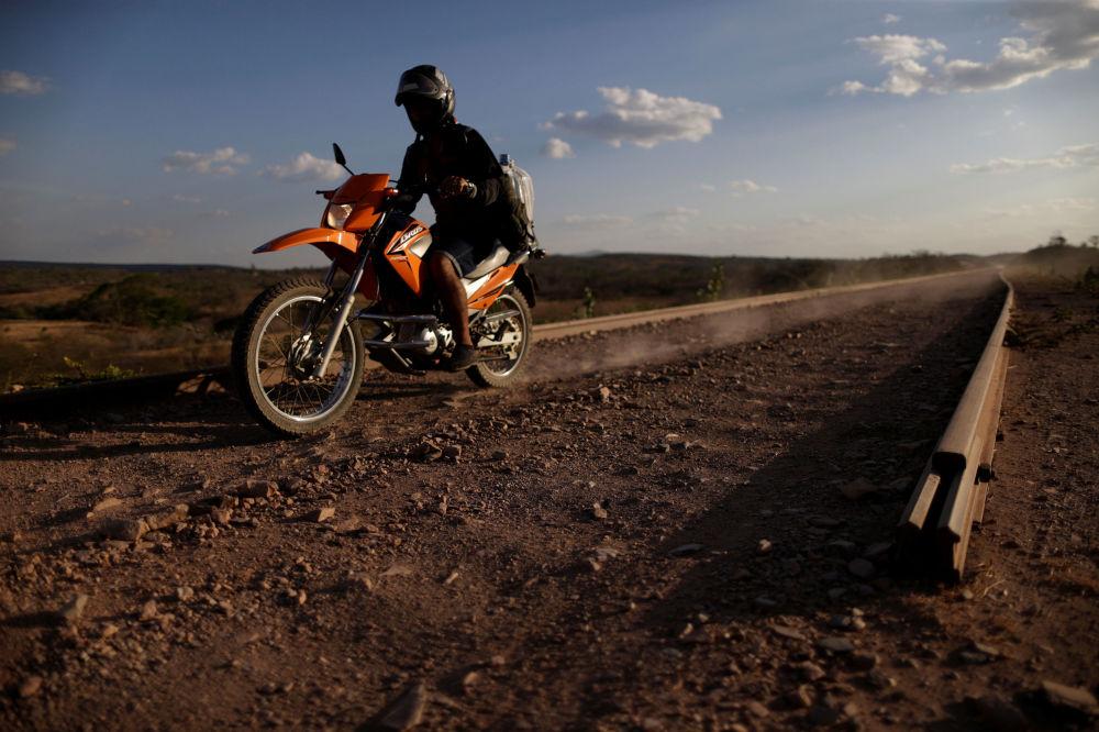 Motocyklista jedzie po niedokończonej kolei Transnordestina do przejazdu wagonów towarowych