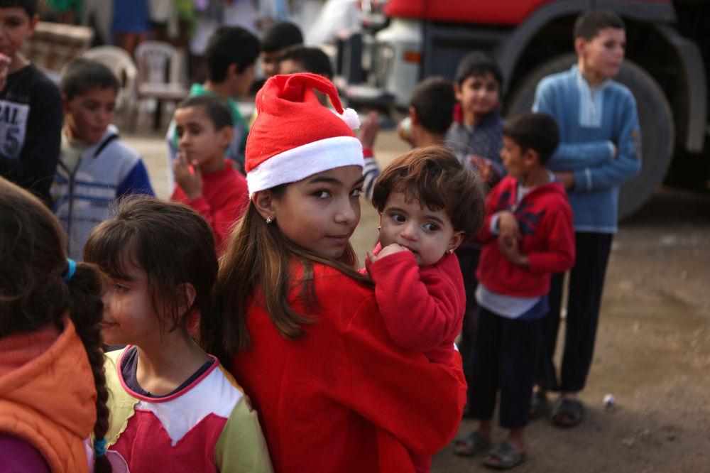 Dziewczyna z Libanu z dzieckiem z Syrii podczas rozdawania prezentów w Bejrucie
