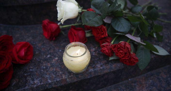 Kwiaty i znicze pod budynkiem Chóru Aleksandrowa w Moskwie