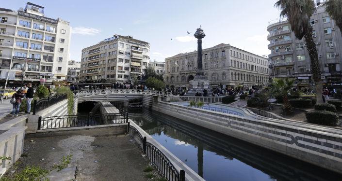 Ludzie na moście nad rzeką Barada w Damaszku