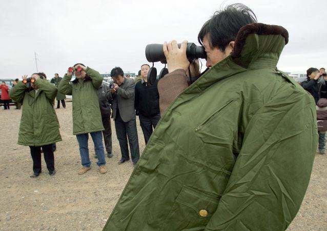 Widzowie oglądają start rakiety z kosmodromu Jiuquan w Chinach. Zdjęcie archiwalne