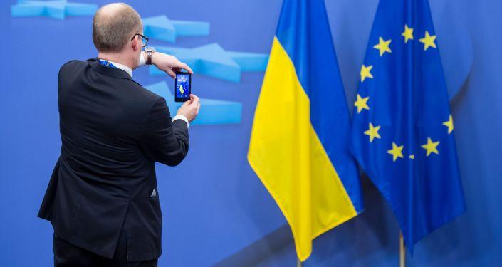 Człowiek fotografuje flagi Ukrainy i Unii Europejskiej