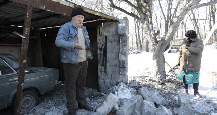 Mieszkańcy w pobliżu garażu uszkodzone w ostrzale Ukraińskich Sił Bezpieczeństwa w mieście Makiejewka w obwodzie donieckim