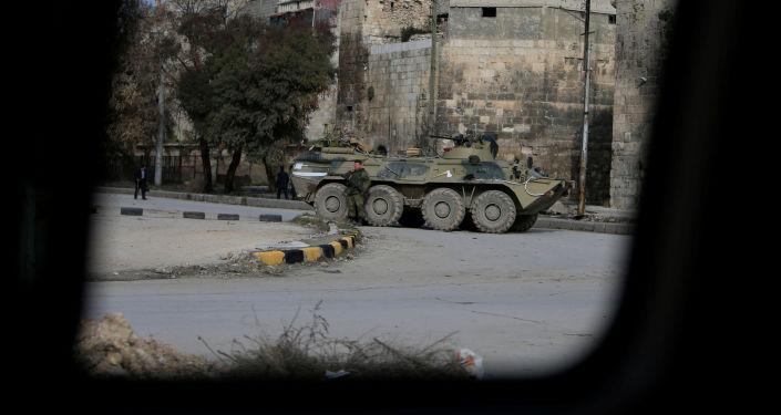 Rosyjski żołnierz stoi obok pojazdu opancerzonego w Aleppo