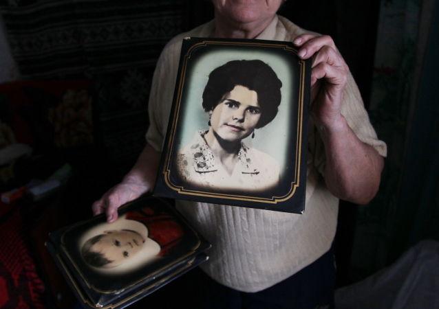 Liubow Tichonowna z wioski Wesołoje pod Donieckiem pokazuje swoją fotografię