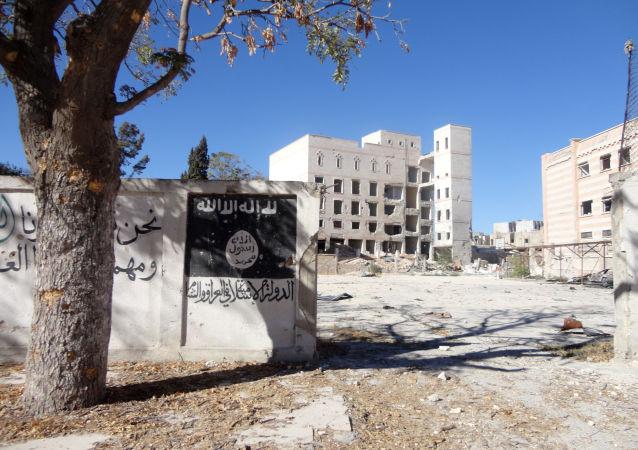 Flaga Daesh namalowana na ścianie w syryjskim mieście Manbidż