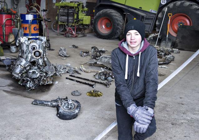 Duński uczeń Daniel Christiansen obok fragmentów znalezionego wraku samolotu z czasów II wojny światowej