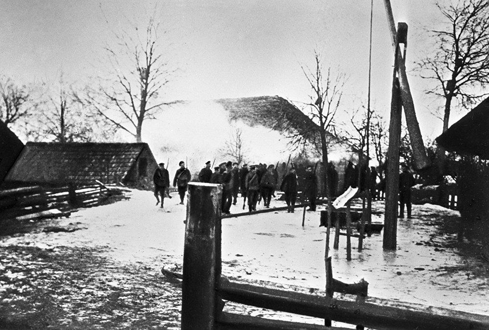 Na wsiach rewolucja, choć w 1917 roku nie zmieniła się w prawdziwą wojnę domową, to już w lutym była krwawa i wyniszczająca.   Żołnierze wchodzą na spalone wiejskie podwórko, należące do uczestnika powstania w krajach nadbałtyckich w 1917 roku.