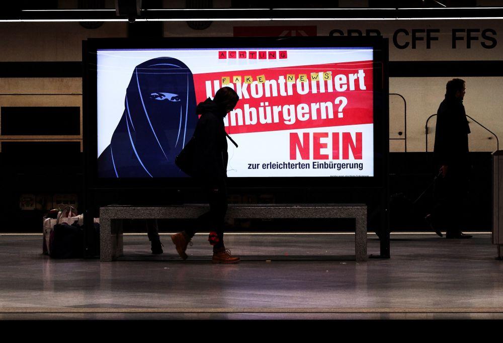 Plakat wyborczy przedstawiający kobietę w burcę na ulicy w Zurychu.