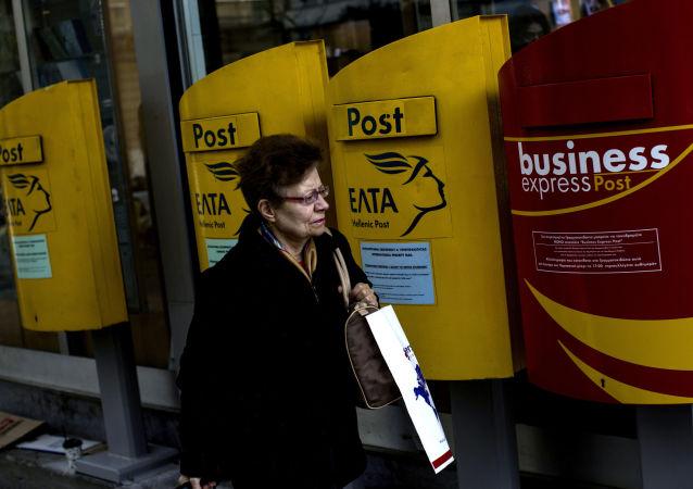 Kobieta obok skrzynek pocztowych w Grecji