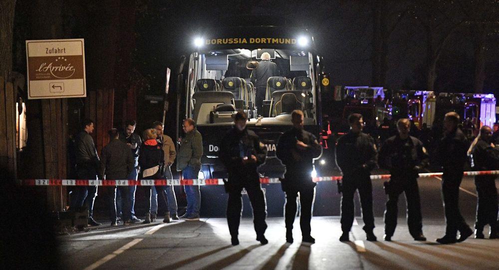 Policja obok autokaru drużyny piłkarskiej Borussia uszkodzonego w wyniku wybuchu w Dortmundzie