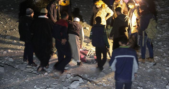 Wolontariusze i ofiary na gruzach po nalocie w Aleppo