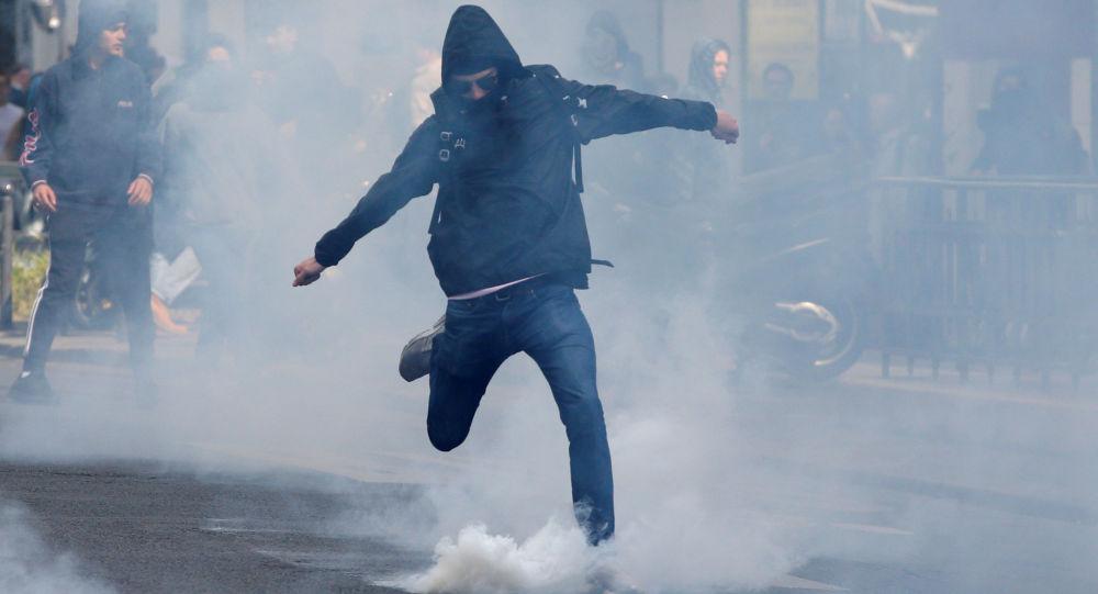 Uczeń kopie spray z gazem łzawiązym w czasie akcji protestu przeciwko Marine Le Pen i Emmanuelowi Macronowi w Paryżu