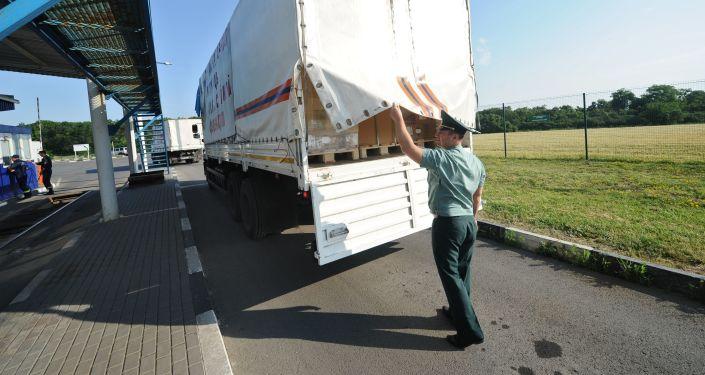 Rosyjski funkcjonariusz straży granicznej sprawdza ładunek na granicy rosyjsko-ukraińskiej w obwodzie rostowskim