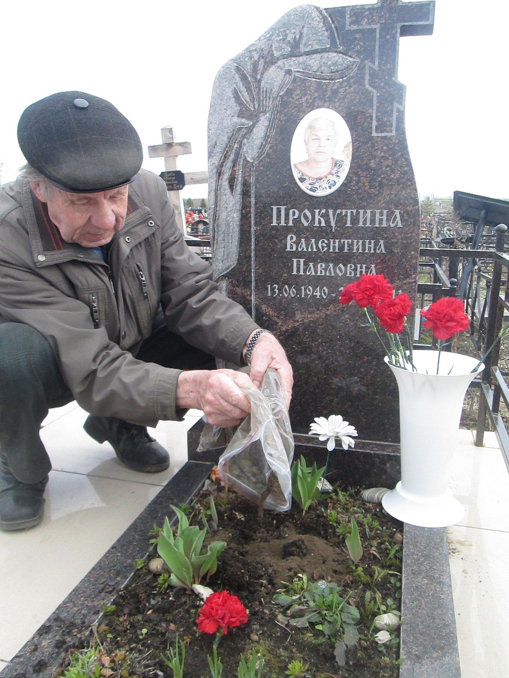 Potomkini czerwonoarmisty Pawła Koczina rozsypuje ziemię na grobie jego żony. Wołogda