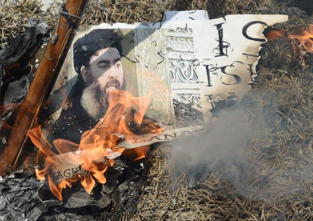 Płonący plakat z wizerunkiem przywódcy ugrupowania terrorystycznego Daesh Abu-Bakr al-Baghdadiego