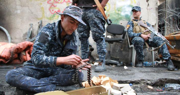 Żołnierz irackiej armii ładuje taśmę nabojową w Mosulu