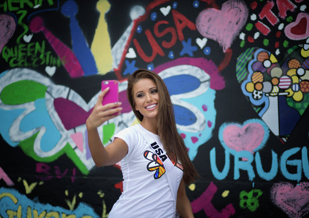 Miss USA, Nia Sanchez, takes a selfie after painting on a wall in Miami's Wynwood area, Sunday, Jan. 11, 2015. Miss Universe contestants visited pop artist Romero Britto's studio for an interactive painting event