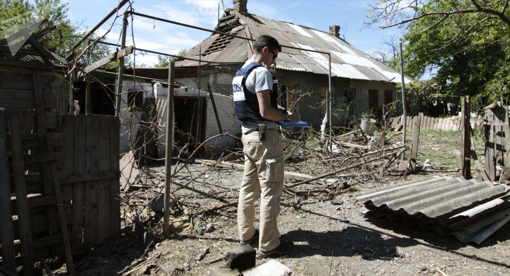 Pracownik OBWE przy domie mieszkalnym, który uległ ostrzałowi. Obwód doniecki