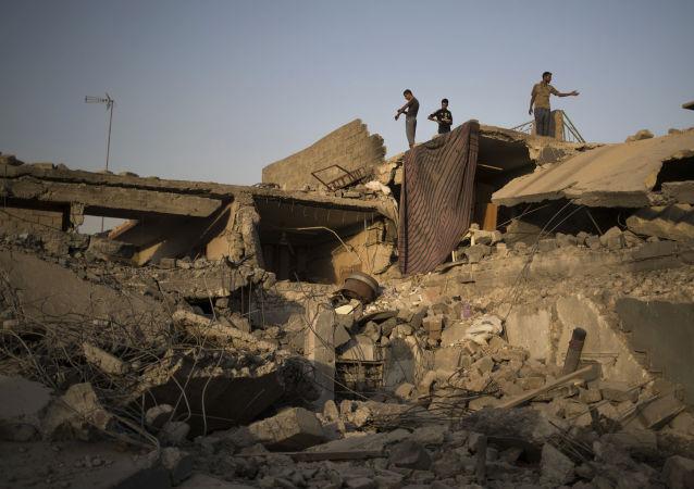 Syryjczycy wśród zrujnowanych budynków na zachodzie Mosulu