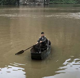 Człowiek w łodzi na jeziorze Sinpyon, Korea Północna