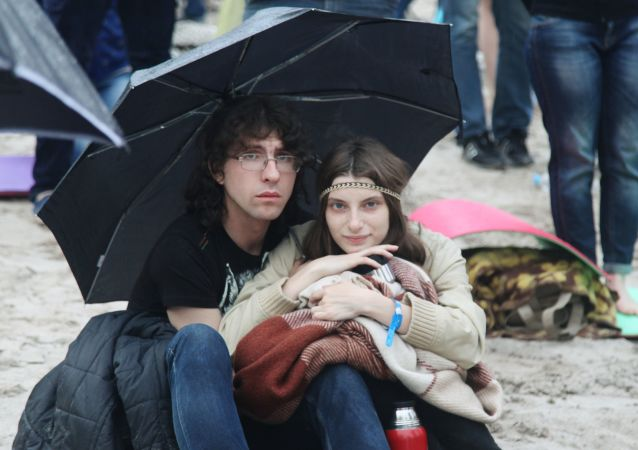 Widzowie chowają się przed deszczem podczas festiwalu Muzyka świata  w Woronieżu.
