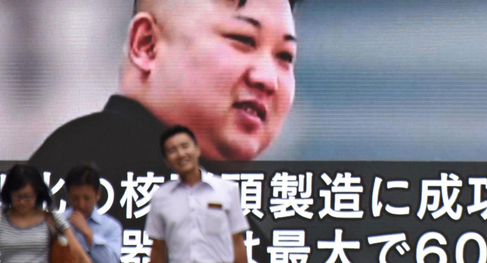 Piesi mijają ogromny ekran z wizerunkiem północnokoreańskiego przywódcy Kim Dzong Una w Tokio
