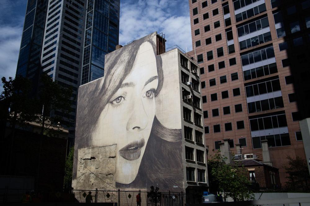 Portret kobiety australijskiego ulicznego artysty pracującego pod pseudonimem Rone na ścianie opuszczonego budynku w Melbourne