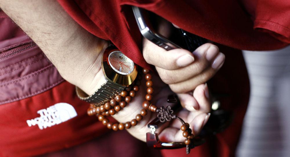 Tybetański mnich z telefonem w Lhasa, Chiny