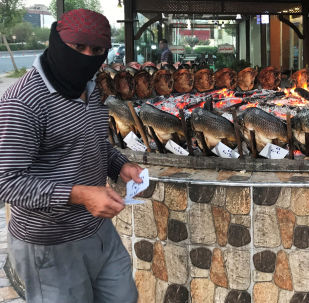 Mężczyzna przyrządza rybę przed sklepem