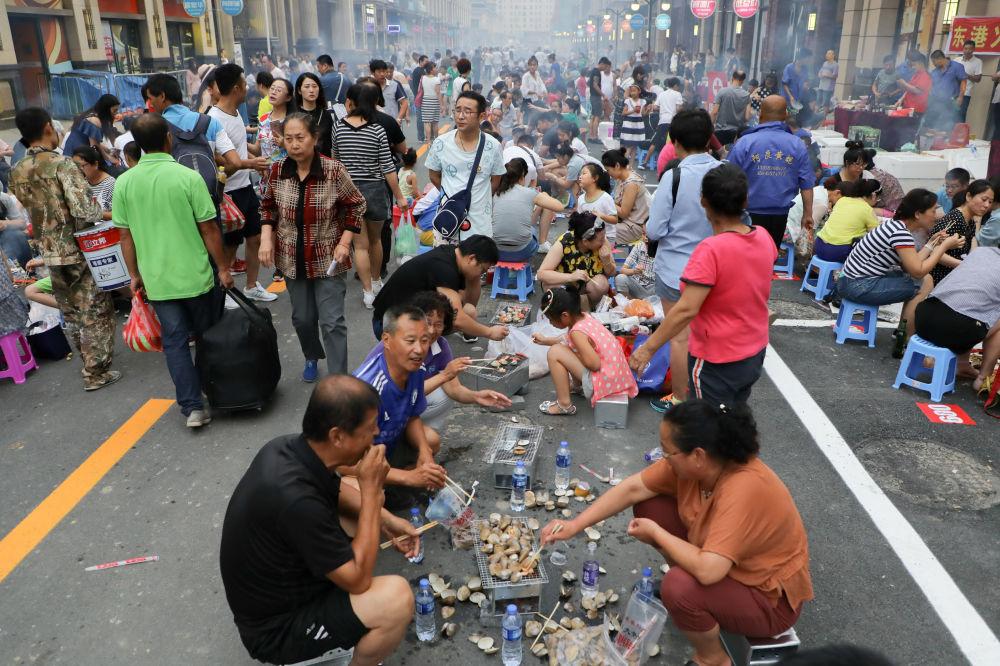 Mieszkańcy Chin gotują i jedzą na ulicy