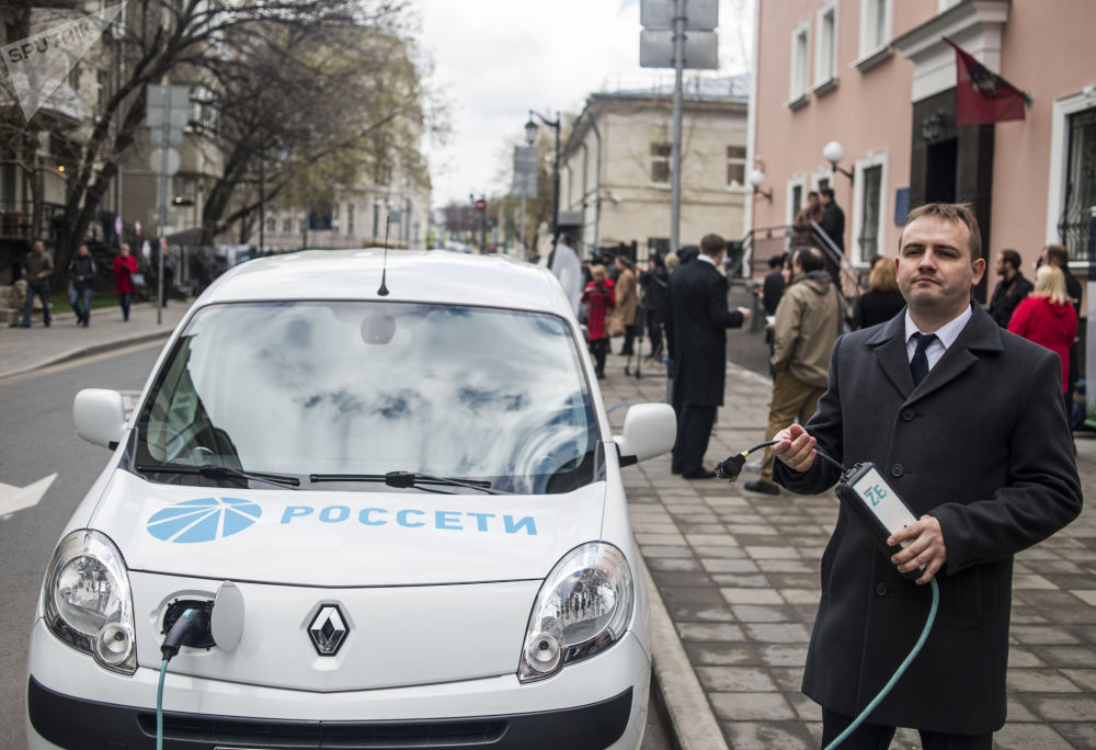 Kierowca ładuje samochód elektryczny na samochodowej stacji ładowania na ulicy Bolszaja Bronnaja w centrum Moskwy