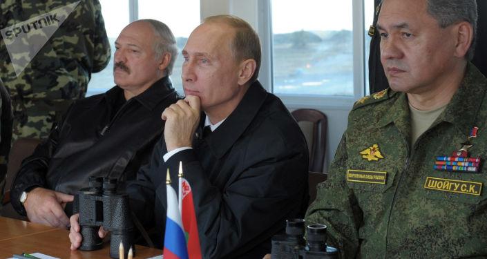 Prezydenci Rosji i Białorusi Władimir Putin i Alaksandr Łukaszenka obserwują przebieg rosyjsko-białoruskich ćwiczeń Zachód 2013 na poligonie Chmielewka w obwodzie kaliningradzkim. Po prawej - minister obrony Rosji Siergiej Szojgu
