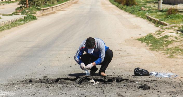 Pobieranie próbek gruntu po ataku w Chan Szejchun w Syrii
