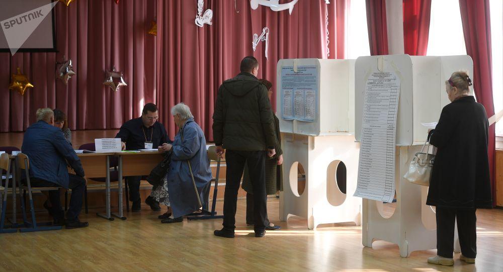 Wyborcy w lokalu wyborczym w Moskwie