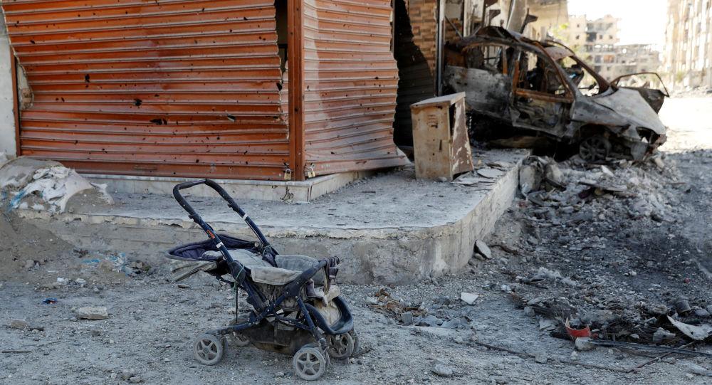 Wózek dla dziecka obok spalonego samochodu w Rakce