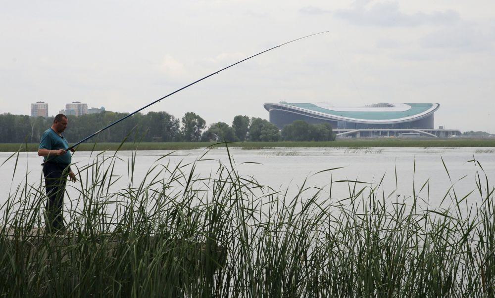 Mężczyzna łowi ryby naprzeciwko stadionu Kazań Arena