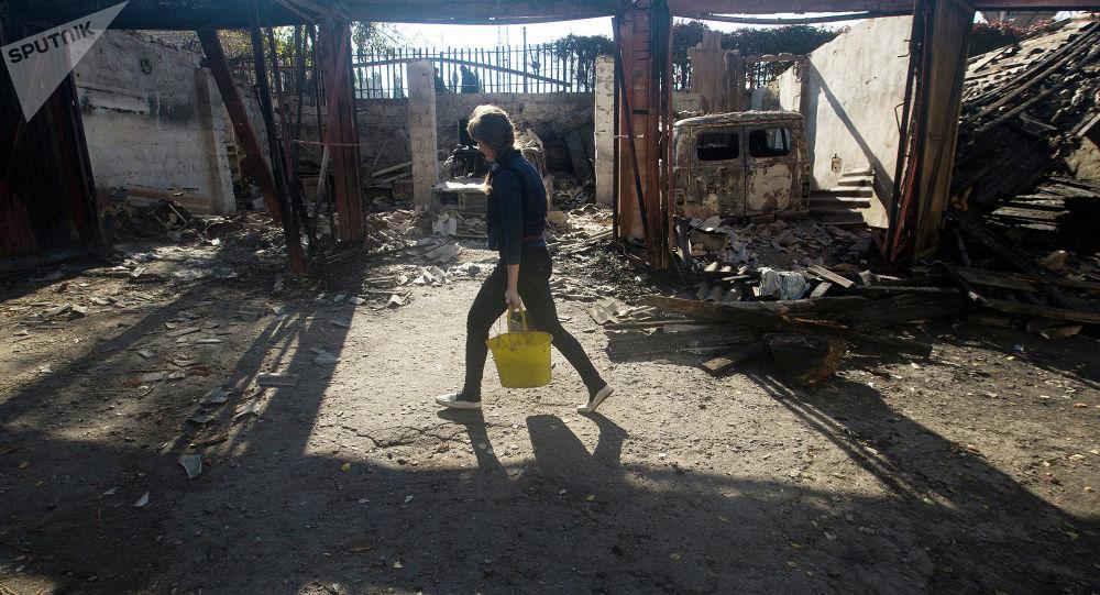 Kobieta niesie wodę we wsi pod Ługańskiem