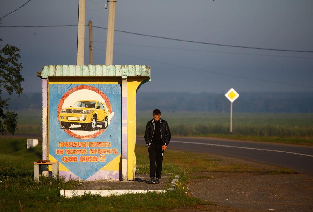 Chłopiec na przystanku autobusowym we wsi Chrapkowo.